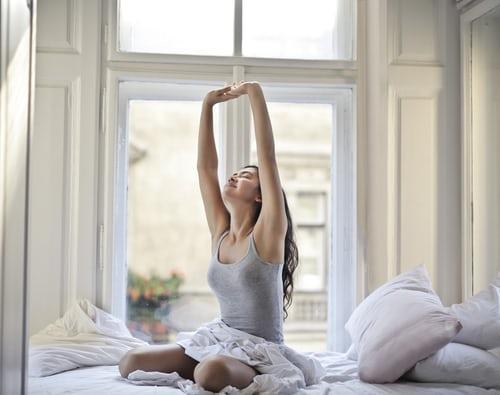 ベッドの上で背伸びをしている女性