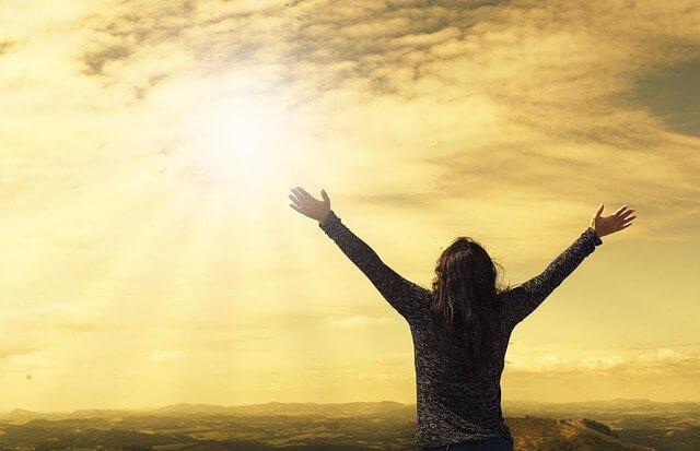 太陽に向かって腕を広げている女性