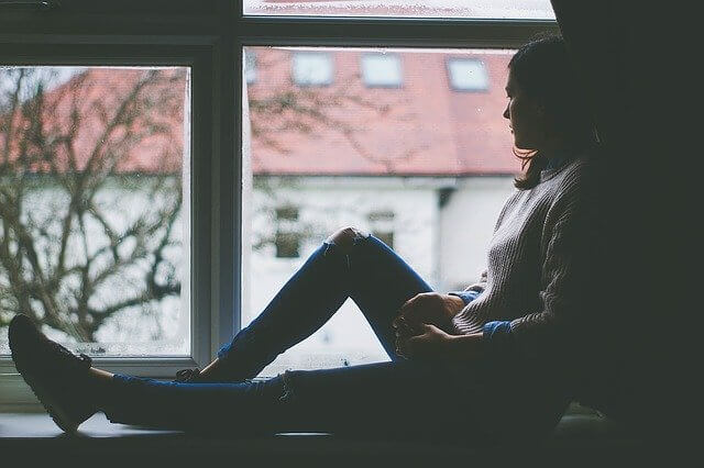 窓際に座っているうつ病の女性