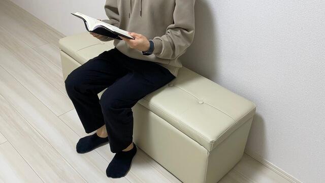 収納スツールの上で読書している僕